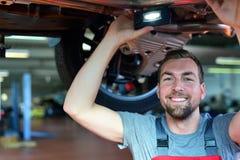 Automechaniker repariert Fahrzeug in einer Werkstatt Lizenzfreie Stockbilder