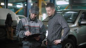 Automechaniker und -kunde, die Diagnose besprechen stock footage