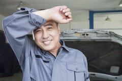 Automechaniker Wiping der Schweiß weg von seiner Braue, lächelnd Stockfotografie