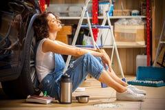 Automechanikerfrau im blauen Overall, der nahe dem Rad von t stillsteht Stockfoto
