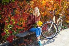 Automne chaud Fille avec la bicyclette et les fleurs Jardin d'automne de bicyclette de femme Loisirs et mode de vie actifs Automn photographie stock
