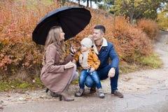 Automne de famille en parc dans le parapluie de pluie Photo stock