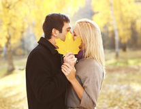 Automne jaune fermant de baiser de feuille d'érable de jeunes couples affectueux de portrait photos stock