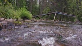 Automnes de cascade, cascade fluide La rivière coule sous un pont en bois, dans le premier plan clips vidéos