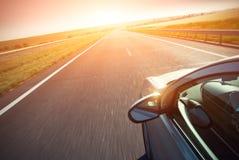 Automobil bewegt sich mit schneller Geschwindigkeit bei Sonnenaufgang lizenzfreie stockbilder