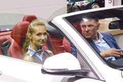 Automobil-Salon-Frau Moskaus internationale mit einem Mann in weißen BMW Stockbild