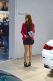 Automobil-Salon Taffic-Frauen Moskaus internationale im kurzen schwarzen Kleid und in einer hochroten Jacke stockbild