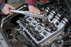 Automobil-, Zylinderkopfinstandhaltung, Mechanikerhände und Werkzeug Stockfotos
