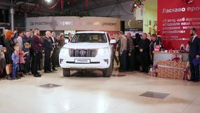Automobilausstellung, neues Fahrzeug fährt in AutoVerkaufszentrum nahe Gästen des Ereignisses stock footage