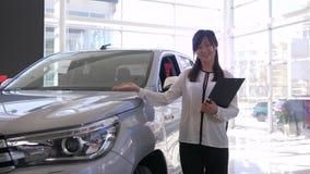 Automobilausstellung, Porträt der lächelnden asiatischen Frau des Autoverkäufers stellt neues Automobil an der Verkaufsstelle vor stock video