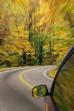 Automobile. Driving down a country road with the autumn colors and a blured affect royalty free stock photography