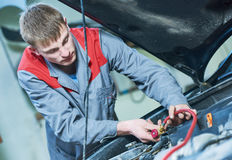 Automobile air-conditioner servicing. mechanic connecting pipes for freon refill. Automobile air-conditioner servicing. serviceman mechanic connecting pipes Stock Image