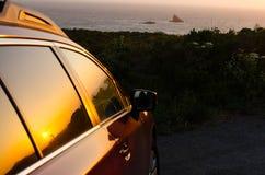 Automobile alla spiaggia durante il tramonto Immagini Stock Libere da Diritti