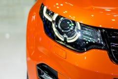 Automobile arancio parcheggiata su un fondo bianco Immagine Stock