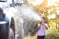 Automobile asiatica felice di lavaggio del genitore di aiuto della ragazza del bambino immagini stock libere da diritti