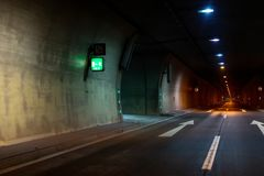 Automobile auto dark car tunnel with white arrows on asphalt showing way direction. Emergency exit sign with many lights