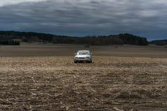 Automobile bianca abbandonata su un campo di grano giallo con le nuvole scure e Immagini Stock Libere da Diritti