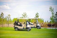 Automobile bianca di golf sul campo verde di golf il bello giorno soleggiato Immagini Stock Libere da Diritti