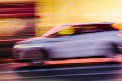 Automobile bianca di SUV in una scena vaga della città Fotografie Stock