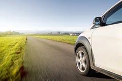 Automobile bianca nel moto che guida sulla strada campestre Immagini Stock Libere da Diritti