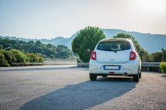 Automobile bianca piccola con l'ottica principale sulla strada principale della strada asfaltata immagini stock libere da diritti
