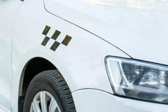 Automobile bianca potata con un taxi di sospiro su  immagine stock