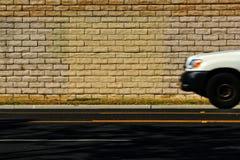 Automobile bianca sulla strada con il muro di mattoni Fotografia Stock Libera da Diritti