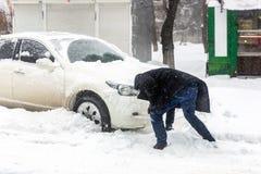 Automobile bloccata con la deriva della neve sulla via della città Equipaggi il veicolo di pulizia da neve con la spazzola durant fotografia stock libera da diritti