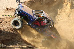 Automobile blu che alimenta su collina ripida, calciando sabbia e polvere Fotografie Stock Libere da Diritti