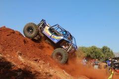 Automobile blu che alimenta sulla montagna ripida della sabbia, ruote anteriori sospese Fotografia Stock