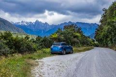Automobile blu sul bordo della strada di paese selvaggio fotografia stock libera da diritti