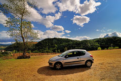 Automobile in brown field. Small silver automobile in brown field with tree, green hills and cloudy sky in background stock photo