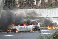 automobile bruciante con i pompieri Fotografia Stock