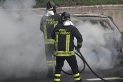 automobile bruciante con i pompieri Immagini Stock