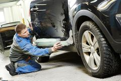 Automobile car body stopping. Repairman worker in automotive industry stopping car body before painting or repaint at auto repair shop Stock Photos