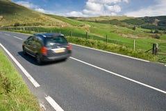 Automobile che accelera sulla strada della montagna nel Galles Immagine Stock