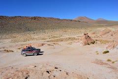 automobile 4x4 che attraversa un deserto della Bolivia Immagine Stock