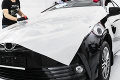 Automobile che avvolge specialista che mette la stagnola o il film del vinile sull'automobile Film protettivo sull'automobile App immagine stock libera da diritti