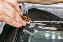 Automobile che avvolge specialista che taglia la stagnola o il film del vinile sull'automobile Film protettivo sull'automobile Ap fotografie stock libere da diritti