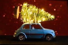 Automobile che consegna l'albero del nuovo anno o di Natale immagini stock