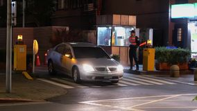 Automobile che lascia parcheggio sotterraneo con il conduttore di traffico che dirige il traffico all'entrata archivi video