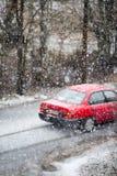 Automobile che passa vicino su una bufera di neve della neve fotografia stock