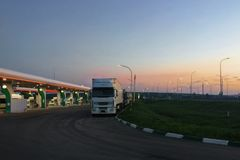 Automobile che rifornisce stazione di combustibile all'alba o nella notte, durante il tramonto, camion nel parcheggio Immagine Stock