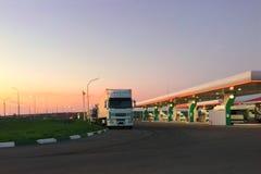 Automobile che rifornisce stazione di combustibile all'alba o nella sera durante il tramonto, camion nel parcheggio Fotografia Stock