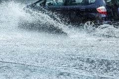 Automobile che si muove con l'alta velocità attraverso la pozza dell'acqua sulla strada sommersa Fotografia Stock Libera da Diritti