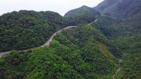 Automobile che si muove lungo la strada Serpentinous curva fra l'ubriacone verde Forest Trees in Taiwan Siluetta dell'uomo Coweri stock footage
