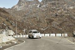 Automobile che viaggia in discesa sulle strade curve della montagna Azionamento di veicolo guidando in un tiro del tornante dall' immagine stock