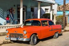 Automobile classica americana in Cuba con la bandiera nazionale da Cuba Immagine Stock