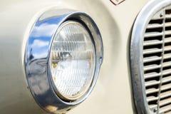 Automobile classica con il primo piano sui fari o sulla lampada del faro di retro stile dell'annata dell'automobile Fotografia Stock