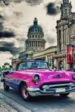 Automobile classica d'annata in una via di vecchia Avana con il Campidoglio in Th Immagini Stock